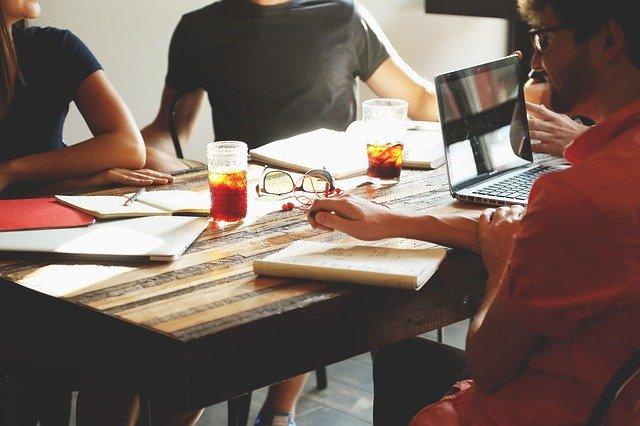 Pessoas ao redor da mesa trabalhando
